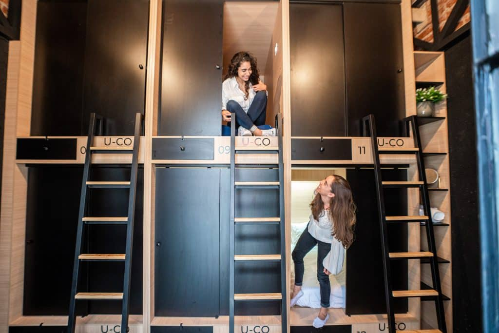 Two young women at a shared room with 6 capsule beds